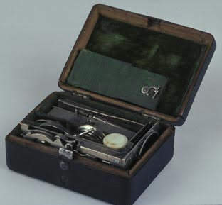 Pocket microscope and accessories packed away in a case less than 6 cubic inches.