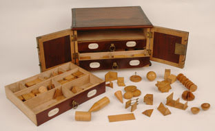 Set of wooden geometric models in a miniature chest of drawers