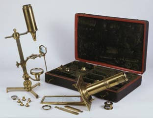 A microscope compendium containing many different parts in a portable case; microscopes are shown assembled in the foreground.