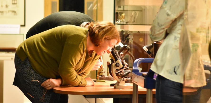 Woman looking into a microscope
