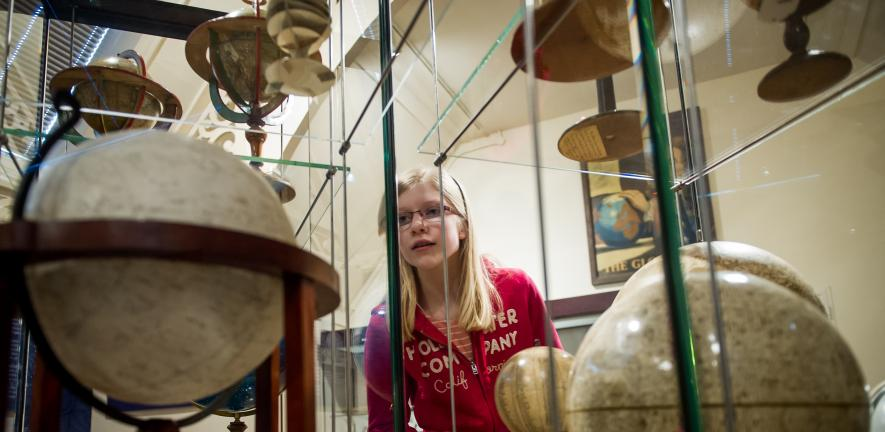 Young person looking at a Globe