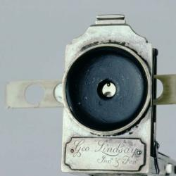 Detail of a collapsible single-lens microscope showing lens and slide