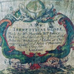 """Detail of globe showing inscription """"A New TERRESTRIAL GLOBE, Made by Rt Morden, Wan Berry, Ph Lea. And Sold at their Shops at the Atlas in Cornhill, at ye Globe at Chering Cross, and at ye Atlas of Hercules in Cheapside, London."""