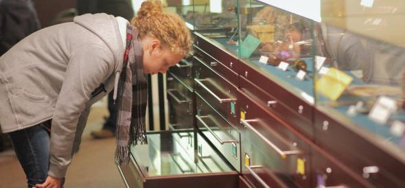Woman looking into an open drawer below a museum display case.