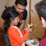 A volunteer shows a child how to use a sextant